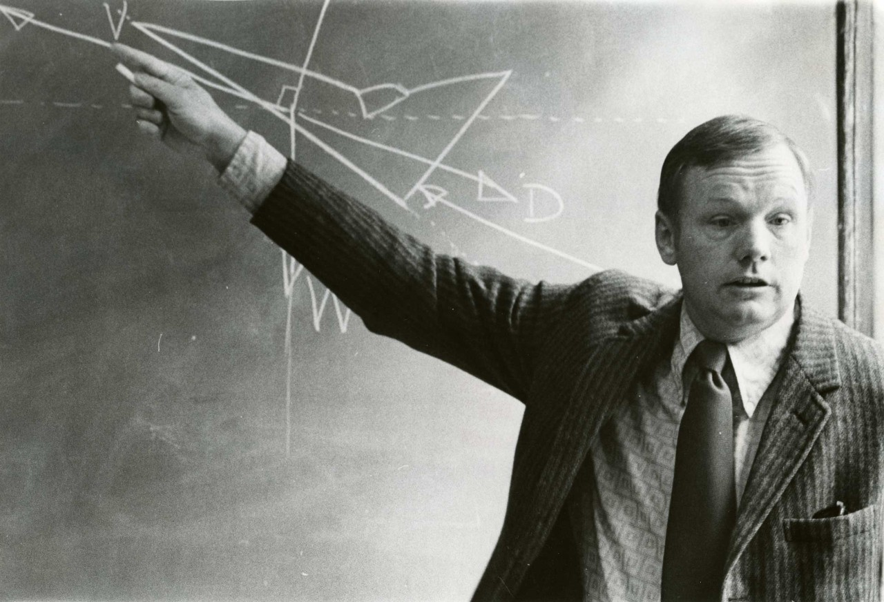Neil Armstrong lectures with diagrams on a chalkboard