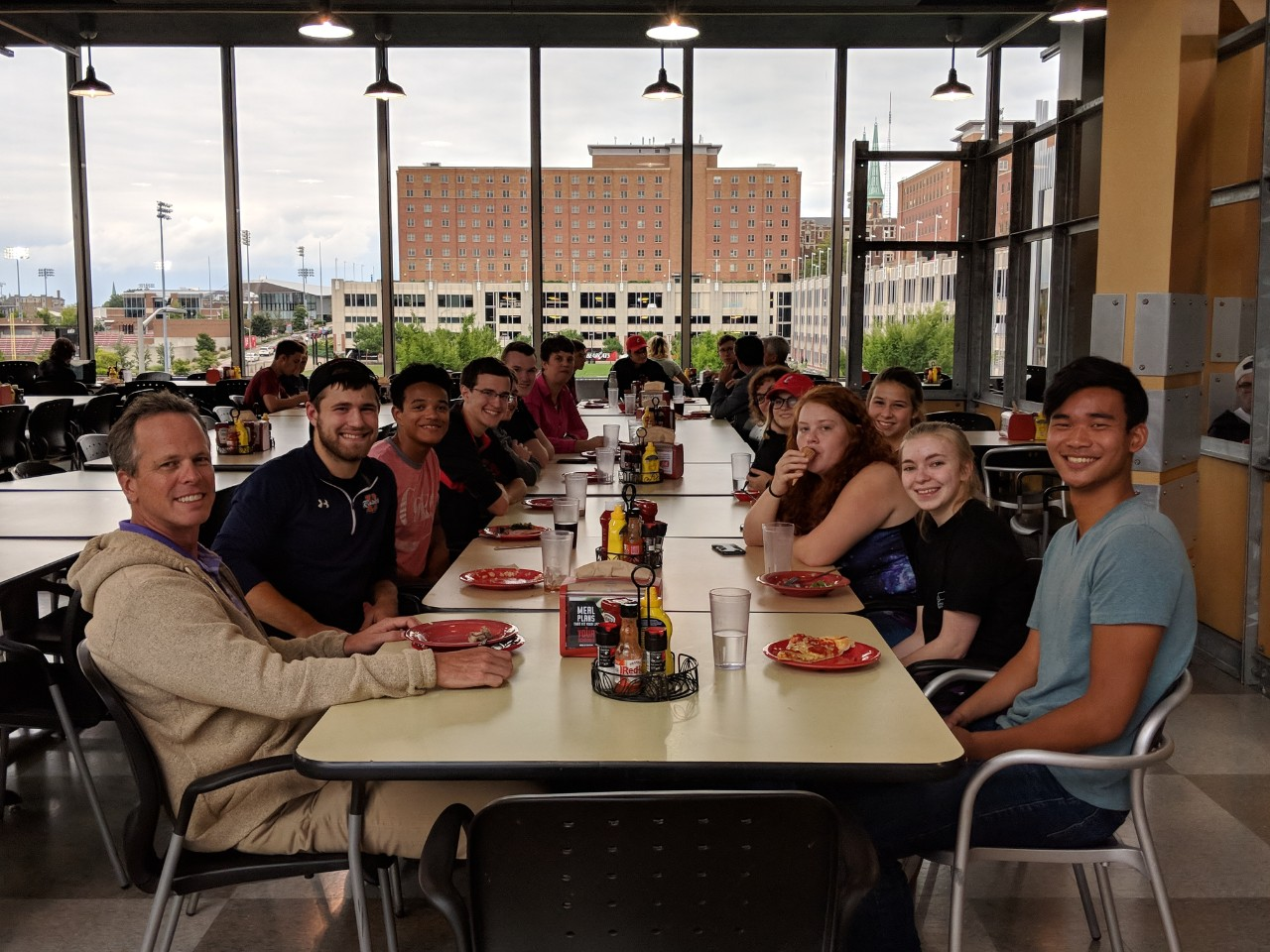about 15 students and faculty members sit around a table eating pizza.