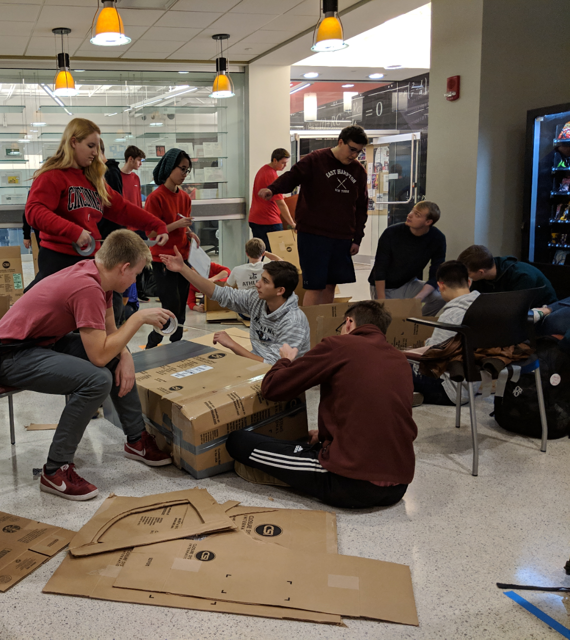 three groups of about a dozen in casual dress, stand and sit in a common area filled with cardboard and chairs.