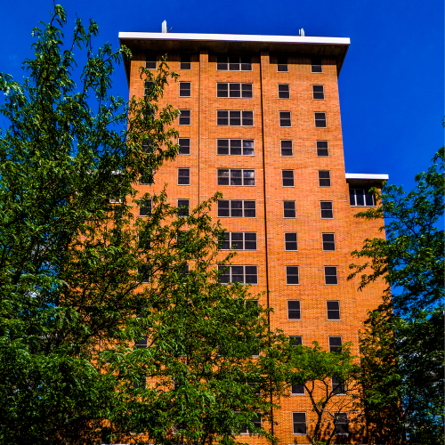 a photo of a tall orange brick tower on a sunny day, against a blue sky.