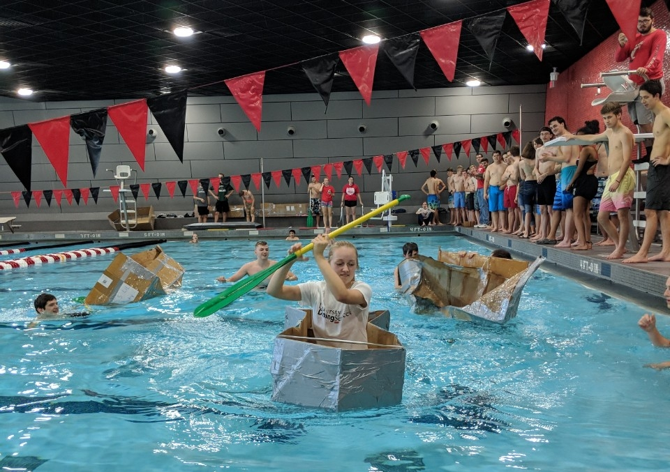 Several students in bathing suits compete in a cardboard canoe race in a UC pool. In the foreground, one young woman is paddling her canoe towards the camera, while two other canoes sink in the background. Groups of people stand on the side of the pool watching.