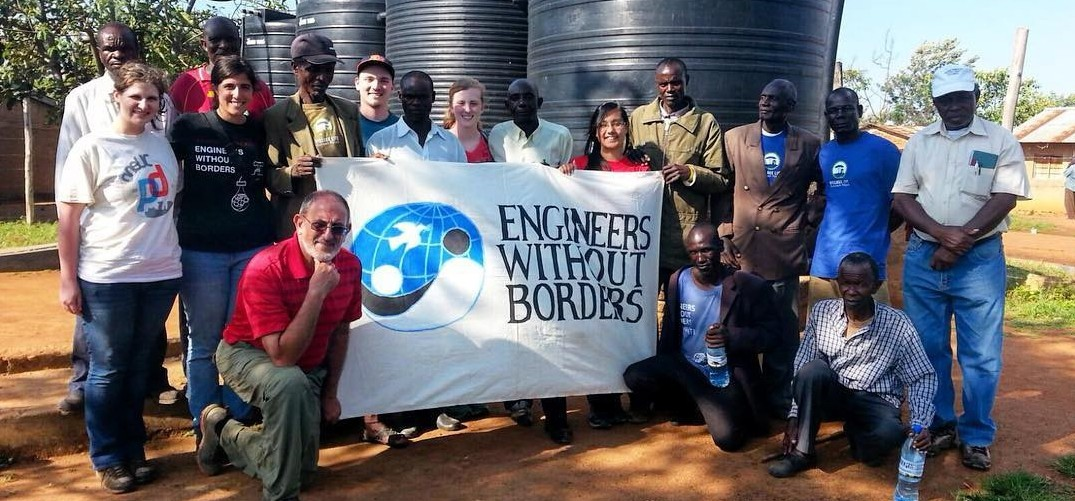 Engineers without Borders-UC Chapter poses for a picture in Tanzania with locals. They are all helping to hold the Engineers without Borders sign.