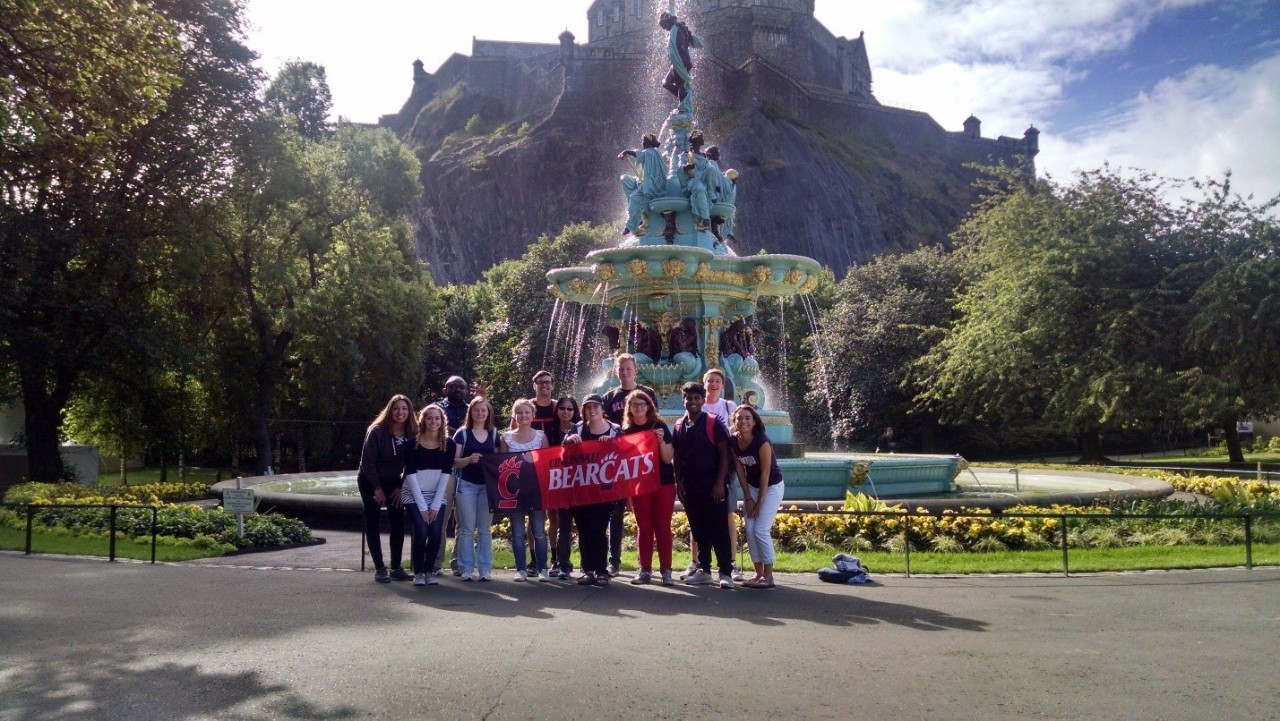 Students posing with a UC flag in front of a fountain in Scotland.
