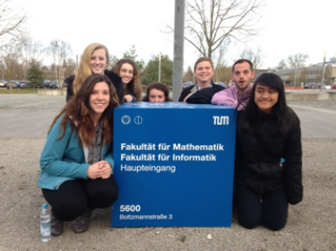Seven UC students post around a sign at the University of Munich.