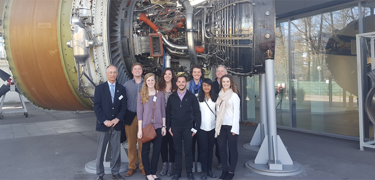 Eight UC students pose with a guide in front of a jet engine.