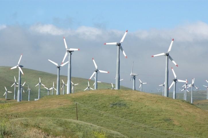 Open, hillside field with windmills
